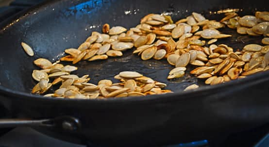 Pumpkin seeds being toasted in a pan with oil.