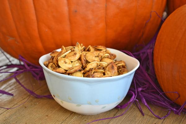 Roasted pumpkin seeds in a white bowl, sitting in front of pumpkins.