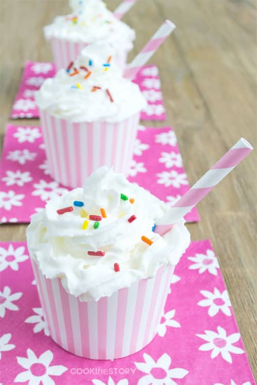 Small pink and white striped cups that are topped with whipped cream and colorful sprinkles, with a straw.