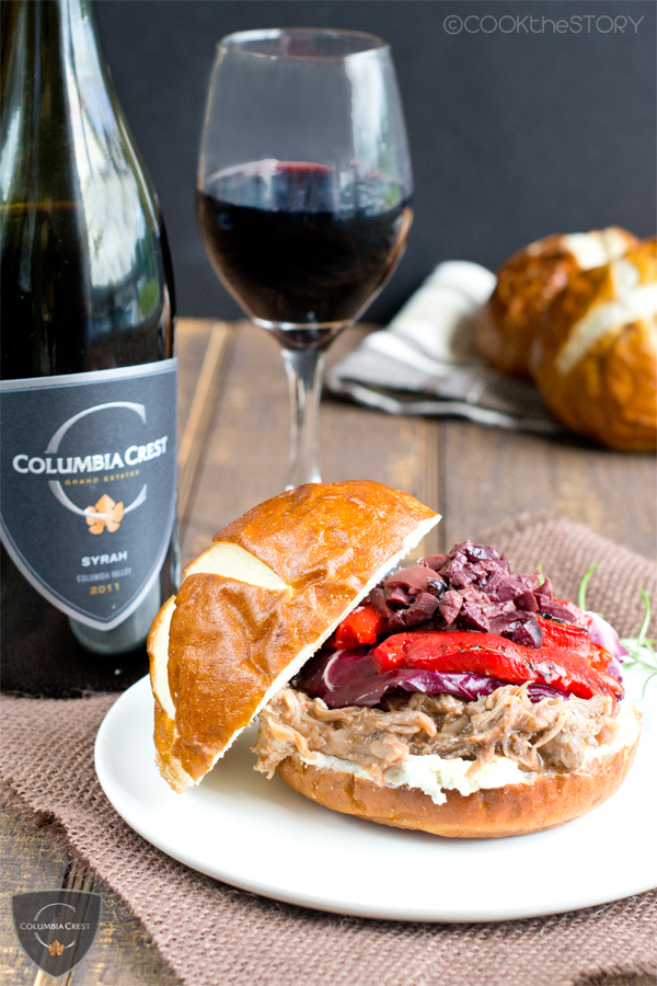 Fancy Pulled Pork Sandwich topped with a goat cheese spread, roasted peppers, radicchio, and tapenade with glass and bottle of red wine.