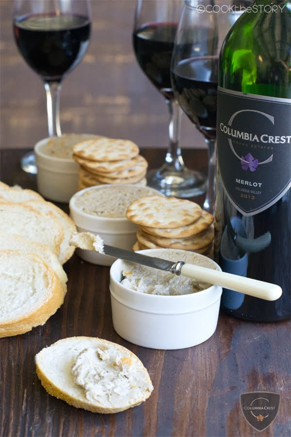 Potted Cheese in small pots, with bread slices and crackers to spread cheese on. Bottle and glasses of red wine in background.