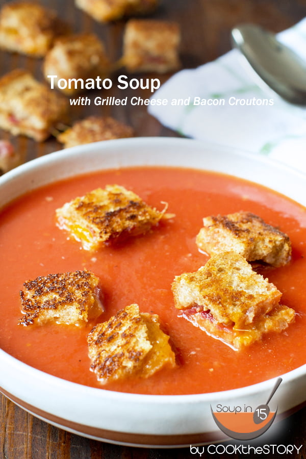 Tomato Soup with Grilled Cheese and Bacon Croutons on top in a white bowl.